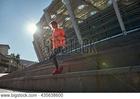 Low Angle Active Sportswoman In Sportswear Use Devices Run Jog On Stairs Steps. Sporty Toned Girl En