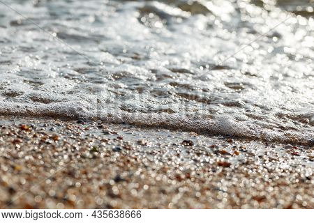 Tidal Bore. The Wave Rolls Onto The Seashore, Which Is Covered With Shells. Coastline. Sea Waves Wit