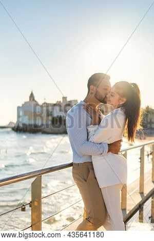 Side View Of Romantic Ethnic Couple Standing Near Railing On Promenade And Embracing Gently On Sunny