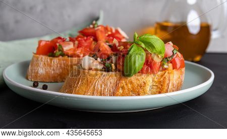 Two Slices Of Tomato Bruschetta Made From Ciabatta Bread With Diced Tomatoes, Basil And Chopped Garl