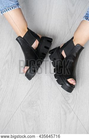 Black Leather Open Sandals With Heels Stand On The Asphalt In The Sun. Womens Shoes With Buckles Wit