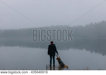 Silhouette Photo Of Man And Dog Staying On Pier On Lake Shore. Fog Above Water And Forest On Backgro
