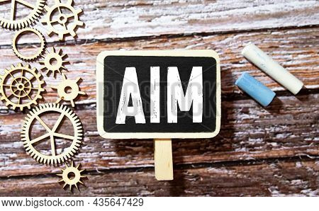 The Word Aim On A Strip Of White Paper. A Red Dart Will Be Stuck In The Word. Blue Background