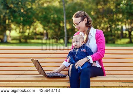 Woman With Child Sits On Park Bench During Telework With Laptop.