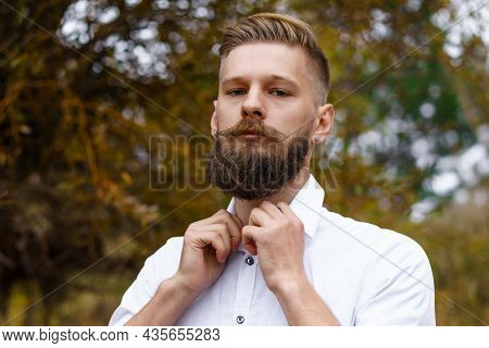 Autumn Mood. Pensive Young Man In White Shirt, Meditates And Walks In Park Against The Backdrop Of B
