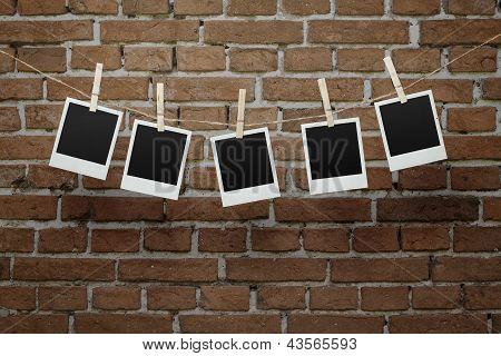 Five Blank Photos Over Bricl Wall