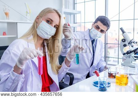 Two Scientists Wears Hygiene Protective Mask Are Working Holding Looking At Test Tube With Sample In
