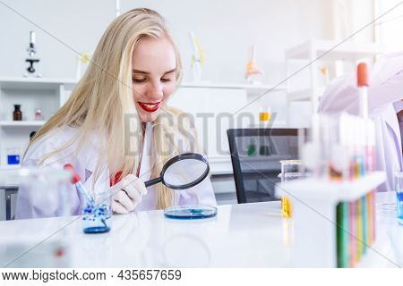 Portrait Of A Female Researcher Carrying Out Research In A Chemistry Lab Scientist Holding Magnifyin