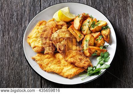 Breaded Chicken Cutlets With Oven Roasted Potato Wedges On A Plate On A Wooden Table, Horizontal Vie