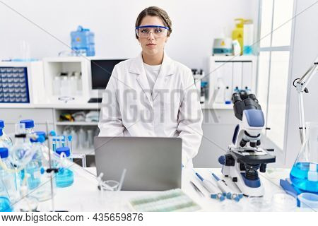 Young hispanic woman wearing scientist uniform working at laboratory thinking attitude and sober expression looking self confident