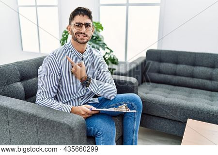 Young psychologist man at consultation office pointing aside worried and nervous with forefinger, concerned and surprised expression