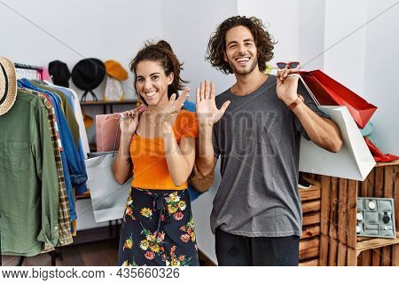Young hispanic couple holding shopping bags at retail shop waiving saying hello happy and smiling, friendly welcome gesture