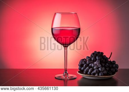 Glass Of Red Wine With Grapes On Plate On Red Bacground With Copy Space. Tasting Of Wine Concept.