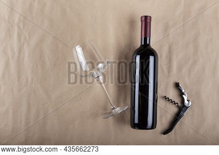 Wine Bottle, Glass And Corkscrew On A Brown Background. Space For Text. Top View.