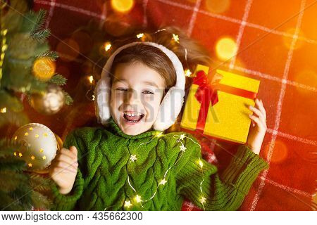 Girl In A Warm Knitted Sweater And Fur Headphones Is Lying On A Blanket Near The Christmas Tree With