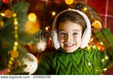 A Happy Girl In Fur Headphones Lies Near The Christmas Tree In Garlands And Lights In A Warm Sweater