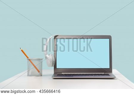 Laptop With Headphones On Wooden Desk. Mockup Screen