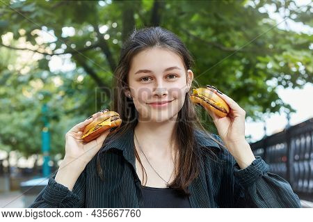 Young Brunette With A Smile Holds Two Cheeseburgers In Her Hands.