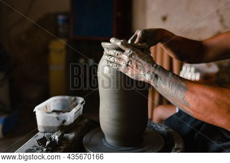 Close-up Of The Hands Of The Craftsman While Creating A Ceramic Pot On The Lathe