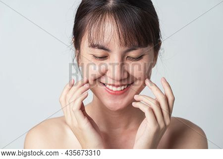 Young Asian Woman Smiling Confident With Freckle On Face And Hand Gently Touching Cheek Applying Ski