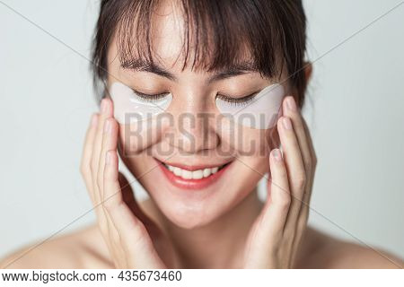 Selective Focus. Asian Woman Smiling And Applying Patches Mask Under Eyes For Anti Wrinkles And Eye