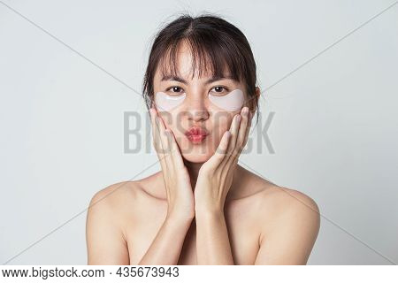 Relaxed Woman Has Fresh Healthy Skin. Asian Woman Wear Collagen Patches Under Eyes. Young Female Joy