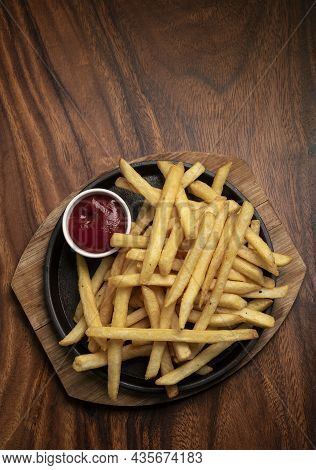 Portion Of French Fries Potato Snack On Wood Table Background With Ketchup In Restaurant