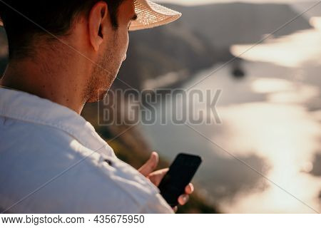 Digital Nomad, Man In The Hat, A Businessman With A Laptop Sits On The Rocks By The Sea During Sunse