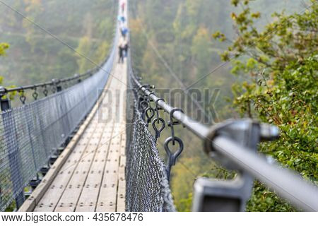 Suspension Wooden Bridge With Steel Ropes Over A Dense Forest In West Germany, Close-up Of A Handrai