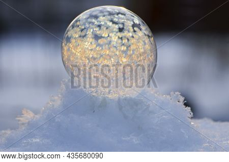A Frozen Bubble In The Snow With Bokeh In The Background. Beautiful Frosty Patterns On A Frozen Soap
