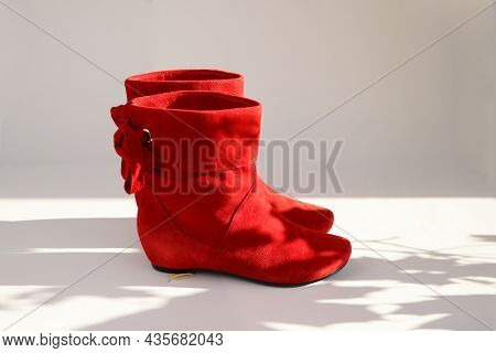 Women's Red Suede Short Angle Boots Without Heels On White Background With Shadow From Leaves. Copy