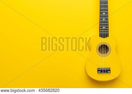 Overhead Photo Of Ukulele With Copy Space. Yellow Colored Wooden Ukulele Guitar. Starter Ukulele On
