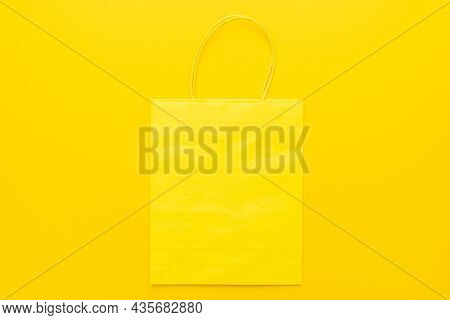 Paper Shopping Bag On The Yellow Background. Top View Image Of Shopping Bag With Copy Space. Flat La