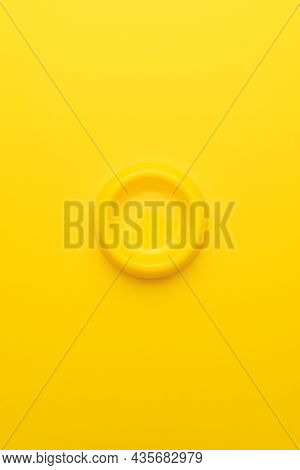 Minimalist Photo Of Yellow Pet Bowl On The Yellow Background. Vertical Orientation Overhead Image Of