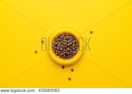 Yellow Pet Bowl Full Of Dry Food On The Yellow Background. Overhead Photo Of Plastic Bowl Full Of Pe