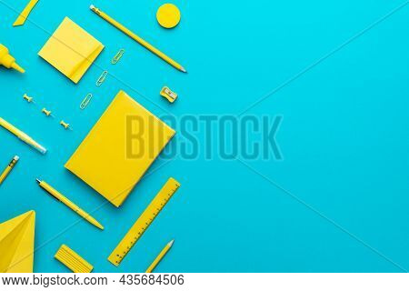 Top View Photo Of Different Yellow Stationery. Stationery Objects Over Turquoise Blue Background. Tr
