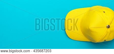 Top View Of The Yellow Baseball Cap Over The Blue Turquoise Background. Minimalist Flat Lay Photo Of