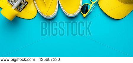 Top View Of Yellow Modern Teenage Accessories. Flat Lay Image Of Yellow Baseball Cap, Sunglasses, Sn