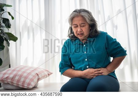 Asian Ederly Woman Sitting On The Bed Is Having A Stomachache Due To Gastritis Disease, On White Bac