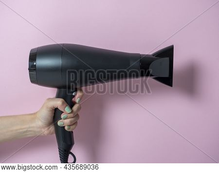 Black Hair Dryer In A Woman's Hand On A Pink Background. Hair Care Product.