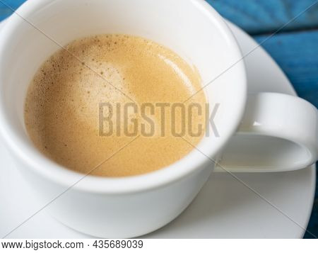 Close-up Of Fragrant And Invigorating Coffee In A White Cup On A Blue Wooden Background.