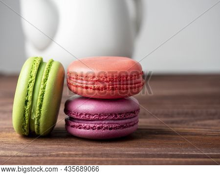 Colorful Delicious Macaroons Lie On A Wooden Table. In The Background Is A White Teapot
