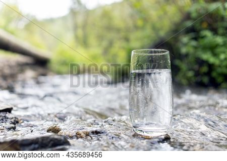 A Glass Of Clean Transparent Drinking Water In A Transparent Glass On A Stone In A Green Forest Near