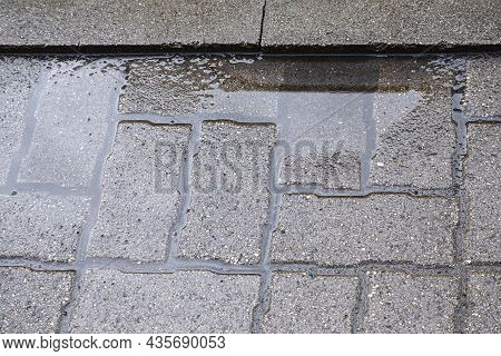 A Puddle After Rain On An Uneven Tile Surface. Improperly Laid Gray Paving Slabs. Errors In Paving S