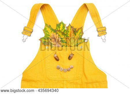 Bunny Composition Made Of A Yellow Overall With Autumn Leaves And Acorns In The Pocket Isolated On W