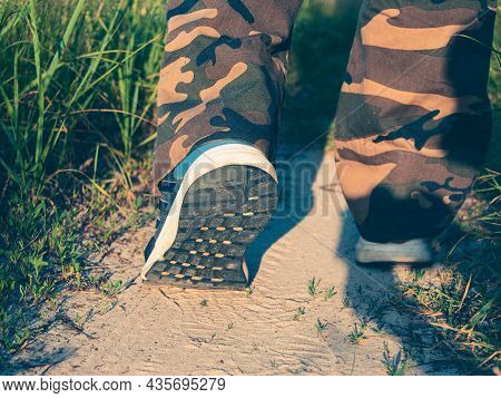 Close-up Of The Legs Of A Man Dressed In Sneakers Walking Along A Path In The Forest. The Concept Of