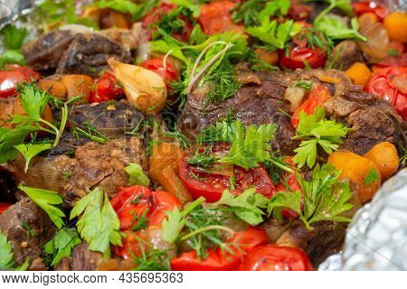 Close-up Of Delicious Juicy Meat Baked In The Oven With Vegetables And Decorated With Fresh Herbs. F