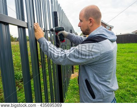 A Man Using A Screwdriver Twists A Metal Picket Fence On The Fence. Worker, Professional, Constructi