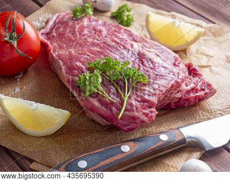 A Piece Of Fresh Raw Beef Lies On Parchment Surrounded By Spices, Herbs And Vegetables. The Knife Is