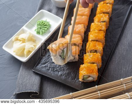 Philadelphia And California Rolls On A Textured Dark Plate. One Roll Is Held In Granny Sticks Above